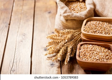 grains and wheat ears on a wooden table, top view