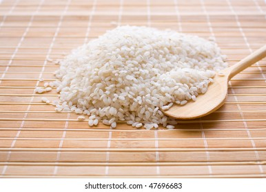 Grains of white rice on a bamboo laying with a  wood spoon.