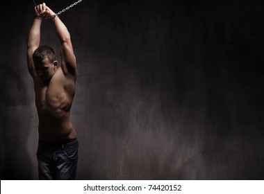 grainy image of a young male model well build with chains over his body