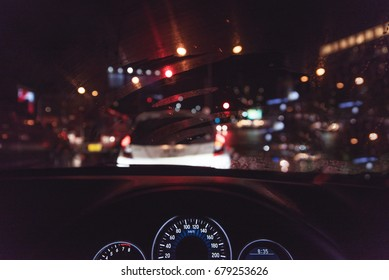 grainy style of car console, waiting in a traffic jam at night with beautiful bokeh and light on vintage tone.