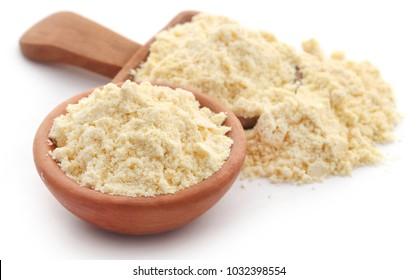 Gram flour in wooden scoop over white background