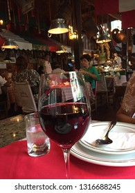 Gramado, Brazil, February 15, 2019: A glass of red wine and a glass of water, which are usually served together, on one with red tablecloth in a traditionally Italian canteen.