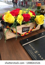 Gramado, Brazil, February 4, 2019: at table 085, in the restaurant of a mall, a natural wooden cachepô with buttons of red and yellow roses, used as decoration. Leaving the environment more beautiful.