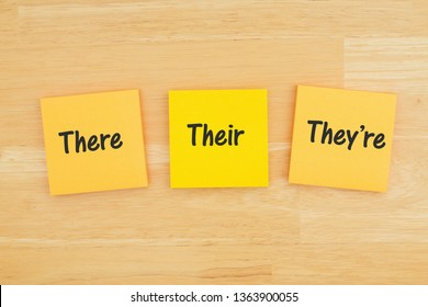 Grammar of  there, their, they're on three sticky notes on textured desk wood