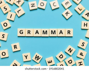 GRAMMAR word made from square letter tiles on blue background.