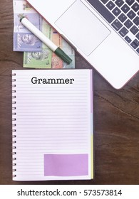 Grammer : Typed Words On a handbook with note book, marker pen and Malaysian Ringgit notes. Vertical view, Vintage and classic mood with wooden table background.