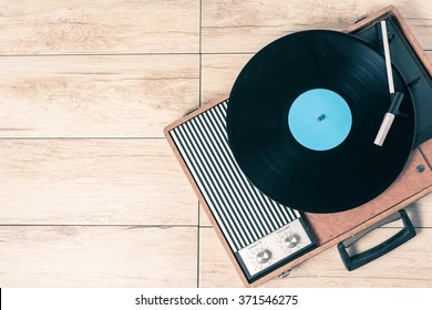 Gramophone with a vinyl record on wooden table, top view and copy space,photo.