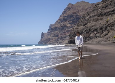 Gran Canaria,  beach Playa de Guigui in the western part of the island, accessible only on foot or by boat; young hiker walking along the waterline