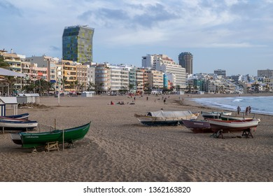 Gran Canaria, Canary islands - march 14, 2019: Fishing boats on the sand and view of buildings in the background of the scene, on Las Canteras beach in the city of Las Palmas de Gran Canaria