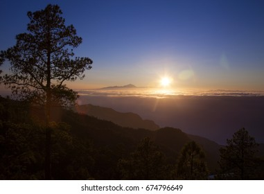 Gran Canaria,  late afternoon light over Teide on Tenerife, the peak of Teide  over the layer of clouds, ocean below