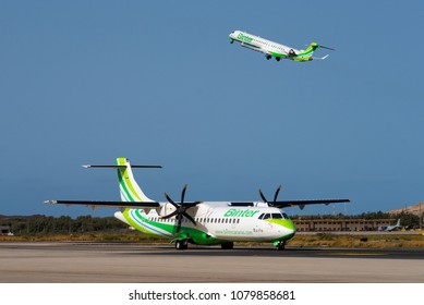 GRAN CANARIA / SPAIN - APRIL 2018 Binter Canarias ATR 72-500 (72-212A), EC-LAD, cn 864 is taxiing for departure while Binter Canarias Canadair CL-600-2E25 Regional Jet CRJ-1000, EC-LOV climbs away.