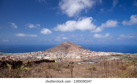 Gran Canaria, view towards volcanic cone of Montana de Galdar, its base surrounded by small multicolored houses of Galdar town