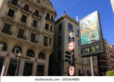 GRANADA, ANDALUSIA, SPAIN - JULY 29, 2017: City billboard with a digital thermometer displaying 45 celsius degree at the intersection of Calle Reyes Catolicos and Calle Padre Suarez streets.