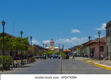 Granada, Nicaragua - April 2, 2014: View of a street with colonial building and the colorful Our Lady of the Assumption Cathedral on the background in the city of Granada, Nicaragua.