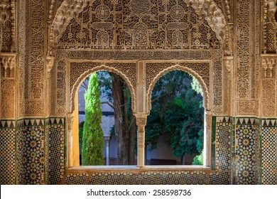 GRANADA, SPAIN - 19 JULY, 2011: View through decorated window to the courtyard in the Alhambra Palace in Granada, Spain on 19 July 2011.