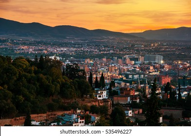 Granada, Spain. Aerial view of Granada - famous city in Andalusia, Spain at night with mountains at the background. It is a UNESCO World Heritage Site and a major touristic attraction
