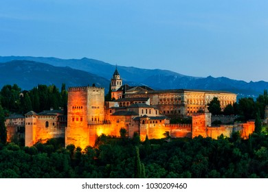 Granada, Spain. Aerial view of illuminated Alhambra Palace in Granada, Spain with Sierra Nevada mountains at the background. Night with clear blue sky