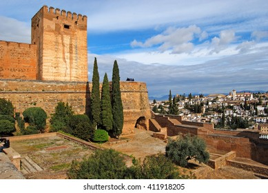 GRANADA, SPAIN - APRIL 11, 2106: Tourists visiting Alhambra, Granada, Spain. Walls of Alcazaba fortress and Granada can be seen.