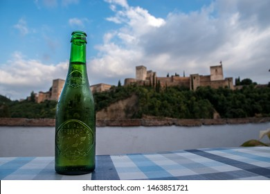 Granada, Spain - ‎July ‎8, ‎2018: A bottle of Alhambra Cerveza (beer) in front of the Alhambra castle