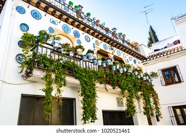 Granada, Spain: Facade of a traditional house with decorative ceramic plates on the wall and balconies full of pots of colorful flowers in the historic Albaycin neighbourhood.
