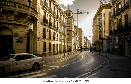 Granada, Spain- February 5,2017: orange facades illuminated by the sun with a taxi in the foreground and a crane in the background on Recogidas street in Granada,it´s a favorite destination for touris