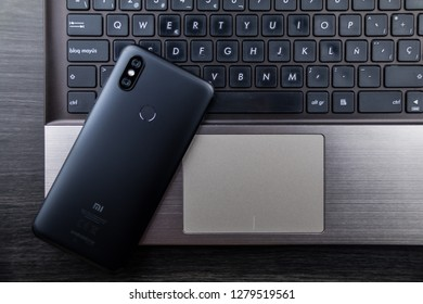 Granada, Spain, January 10, 2019: Modern notebook and smartphone, Mobile with dual camera and fingerprint reader. Xiaomi Mi A2