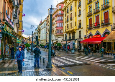 GRANADA, SPAIN, JANUARY 3, 2016: people are strolling through center of the old town of granada dutring cloudy and rainy day