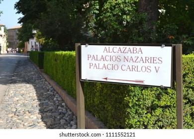 """GRANADA, SPAIN - JULY 15, 2017: Direction sign for """"Alcazaba"""" (Eng. citadel), """"Palacios Nazaries"""" (Eng. Nasrid Palace) and """"Palacio Carlos V"""" (Eng. Palace of Charles V) in Alhambra Palace Complex"""