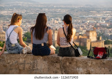 GRANADA, SPAIN - JUNE 24, 2018: Unidentified group of women enjoy the sunset over Granada with Alhambra from viewpoint