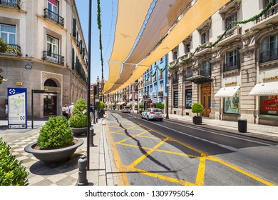 Granada, Spain - June 25, 2018: Street in the historic center of Granada with shops, Spain