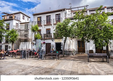GRANADA, SPAIN - JUNE 5, 2018: Granada Plaza san Miguel Bajo - rectangular plaza with outdoor restaurants offering typical Spanish food and Iglesia de San Miguel Bajo.