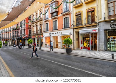 GRANADA, SPAIN - JUNE 5, 2018: View of calle Reyes Catolicos in heart of commercial Granada with numerous cafes and shops. Sun shades over street Reyes Catolicos to protect for intense summer heat.