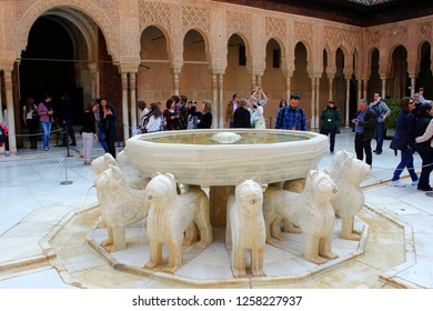 GRANADA, SPAIN - MARCH 14, 2015: groups of tourists taking pictures in Patio de los leones. Alhambra of Granada, Spain. Alhambra of Granada is one of the most known and visited monuments in Spain.