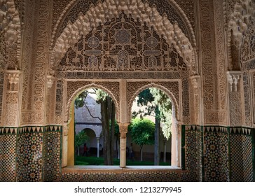 Granada, Spain - May 07 2018: Windows to the green courtyard from ornate decorated interior of Alhambra palace