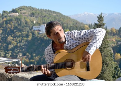 GRANADA, SPAIN - NOVEMBER 12, 2015: Performing flamenco street musician at Mirador de San Nicolas, a famous viewpoint in the district of Albaicin, with Sierra Nevada mountain range in the background