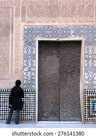 GRANADA, SPAIN - November, 18: Tourist looking at carved islamic wall filled with colourful tiles in Alhambra on November 18, 2010 in Granada, Spain.