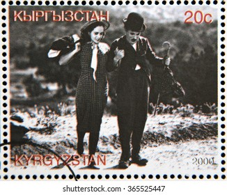 "GRANADA, SPAIN - OCTOBER 19, 2015: A stamp printed in Kyrgyzstan shows Paulette Goddard and Charles Chaplin in the movie ""Modern Times"", circa 2000"