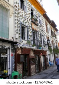 Granada, Spain - September 28, 2018: Man admiring wall tiled with colorful ceramic tiles in town in Andalusia
