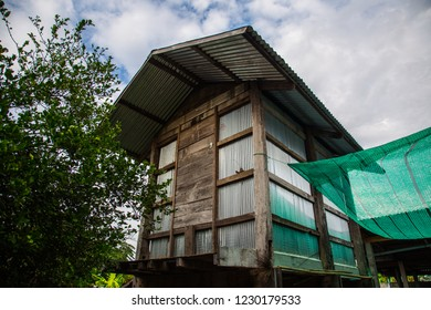 A granary or barn made from old wood and zinc walls in a village in the northeast of Thailand against could sky background