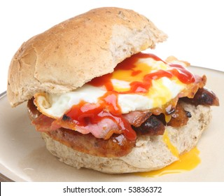 Granary bread roll with fried egg, bacon, sausage and tomato ketchup.