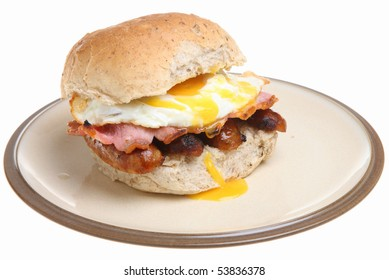 Granary roll with sausages, bacon and fried egg.