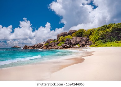 Grand Anse exotic beach at La Digue island in Seychelles. White sandy beach with blue ocean lagoon, white waves and granite rocks in background
