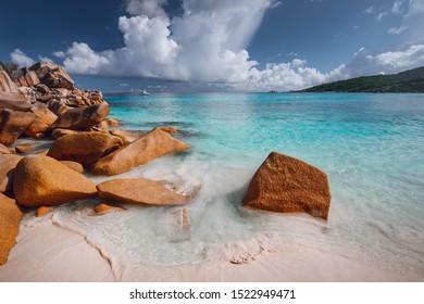 Grand anse, La Digue island, Seychelles. Sandy beach with orange granite boulders and azure ocean lagoon and beautiful cloudscape