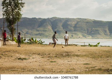 'Grand Anse' region / Haiti - February 9, 2018: Kids playing soccer in a sand field. Valley and mountains in the background. Sky with clouds.