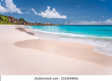 Grand Anse sandy exotic beach at La Digue island in Seychelles. Unrecognized tourists swimming and relax in blue lagoon in background
