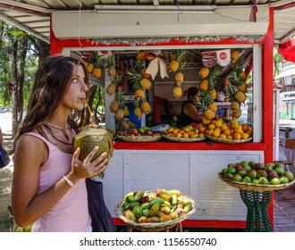 Grand Baie, Mauritius - Jan 10, 2017. A young woman drinking coconut in Grand Baie, Mauritius. Mauritius is a major tourist destination, ranking 3rd in the region.