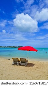 Grand Baie, Mauritius - Jan 3, 2018. Relaxing chairs and red umbrella on beach in Grand Baie, Mauritius. Mauritius is a major tourist destination, ranking 3rd in the region.