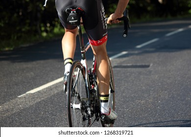 GRAND BORNAND, HAUTE SAVOIE / FRANCE JUILY 17 2018 : on the paved road, a professional cyclist on his bike, seen sitting back and mainly his legs