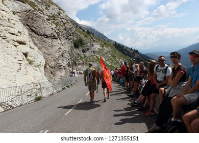 GRAND BORNAND, HAUTE SAVOIE / FRANCE JUILY 17 2018 : on the descent of the colombière pass in haute savoie, spectators sit on the edge of the road waiting for the passage of the Tour de France 2018