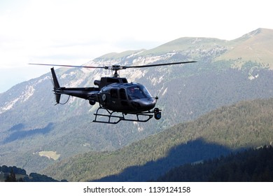 GRAND BORNAND, HAUTE-SAVOIE / FRANCE JUILY 17 2018 : background of mountains and forest in the background, image of the helicopter gray france tv sport, we distinguish very well his pilot